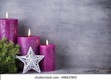 Three purple candles on gray background, Christmas decoration. Advent mood.