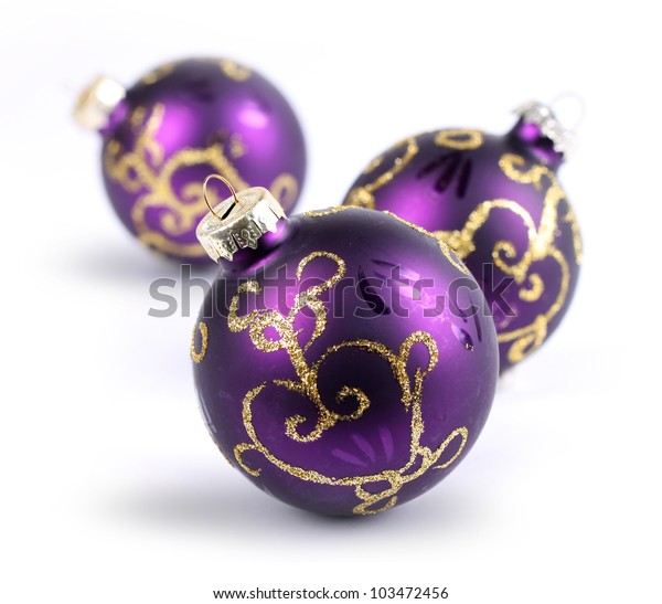 Three purple Christmas balls on white, shallow DOF