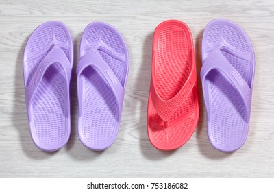 Three purple flip flops and an unpaired upside-down red one on a wooden white background