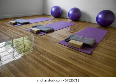 Three purple mats on a yoga classroom