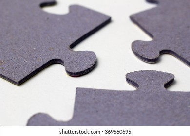 three puzzle pieces close up on paper