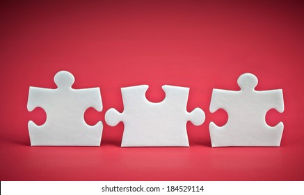 three puzzle pieces on red background