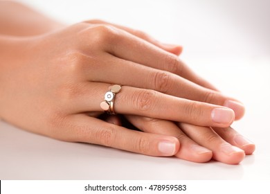 Three puzzle rings in three colors (gold, silver, bronze) on hand of young woman. one of ring has a diamond