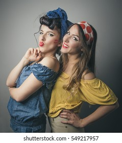 Three quarter body portrait of two happy young female friends in retro clothing smiling and pouting lips, studio background