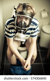 Three quarter body portrait of young boy sat on toilet wearing gas mask for the smell, sepia tone