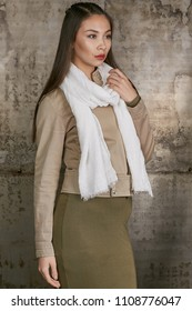 Three quarter isolated studio portrait of a young Asian lady in an olive skirt, a beige jacket and a white scarf. The brunette girl posing against the grunge rusty background, looking to the side.