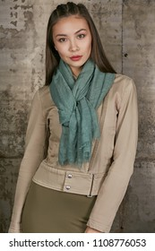 Three quarter isolated studio portrait of a young Asian lady in an olive skirt, a beige jacket and a sage scarf. The brunette girl posing over the grunge rusty background, looking at the camera.