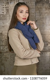 Three quarter isolated studio portrait of a young Asian lady in an olive skirt, a beige jacket and a navy blue scarf. The brunette girl posing over the grunge rusty background, looking at the camera.