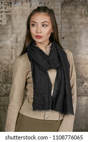 Three quarter isolated studio portrait of a young Asian lady in an olive skirt, a beige jacket and a black scarf. The brunette girl posing over the grunge rusty background, looking to the side.