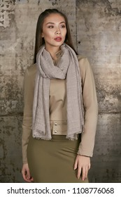 Three quarter isolated studio portrait of a young Asian lady in an olive skirt, a beige jacket and a grey scarf. The brunette girl posing over the grunge rusty background, looking to the side.