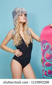 Three quarter isolated studio portrait of a young lady in a black monokini and a grey trapper hat. The blonde girl with long curly hair, standing with a snowboard, posing against the teal background.