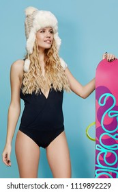 Three quarter isolated studio portrait of a young lady in a black monokini and a beige trapper hat. The blonde woman with curly hair, standing with a snowboard, posing against the teal background.