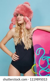 Three quarter isolated studio portrait of a young lady in a black swimsuit and a pink fur hat. The blonde girl with long curly hair, standing with a snowboard, posing against the teal background.