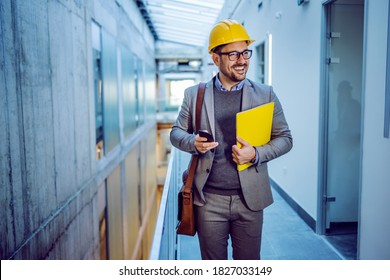 Three quarter length of handsome positive dedicated architect with folder in hands walking in building in construction process. That building is planned to be big business center.