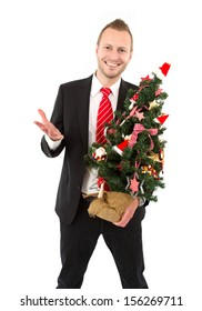 Three quarter length of man holding Christmas tree and questioning