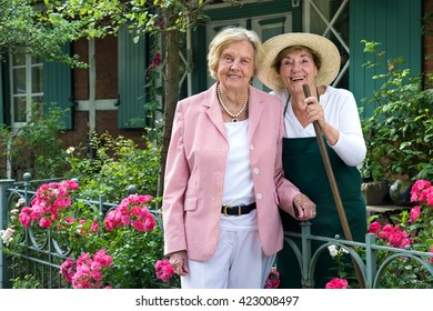 Three Quarter Length Portrait of Two Smiling Senior Women Standing Together in Garden with Bright Pink Flowers