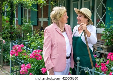 Three Quarter Length Portrait of Two Smiling Senior Women Talking Together in Garden with Bright Pink Flowers