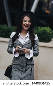 Three quarter length vertical portrait of laughing young woman with mobile phone looking away, while standing near the cafe. Cheerful girl is watching funny video on cell telephone during free time