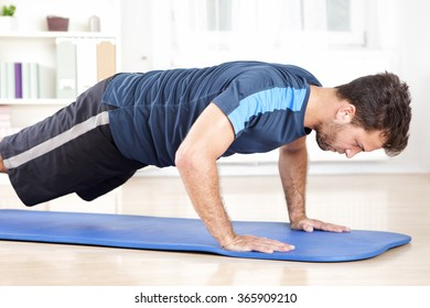 Three Quarter Shot in Side View of an Athletic Young Man Doing an Indoor Push Up Exercise on a Mat.