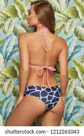 A three quarter shot of a young Caucasian lady with long brown curly hair. The back view of pretty girl with natural makeup, in mismatched swimsuit posing on exotic background, looking to the side.