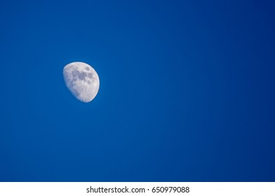 Three quarters of the moon isolated on the blue background