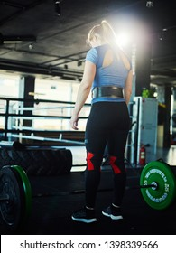 Three quarters rear view of strong young woman wearing weightlifting belt standing by barbell with plates in lamp light. Female athlete getting ready to lift barbell during workout in gym