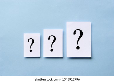 Three question marks of different size printed on white cards arranged in ascending order centered on a blue background in a conceptual image
