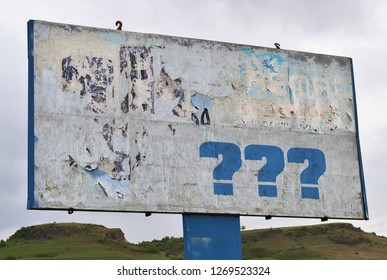 Three question marks on a big board by the road