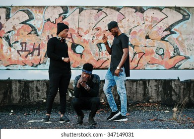 Three rap singers band on the roof background graffiti wall
