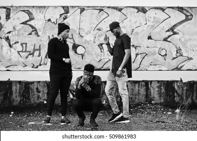 Three rap singers band on the roof background graffiti wall. Black and white photo