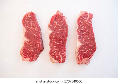 Three Raw Beef Strip Loins Side by Side on a White Quartz Kitchen Countertop