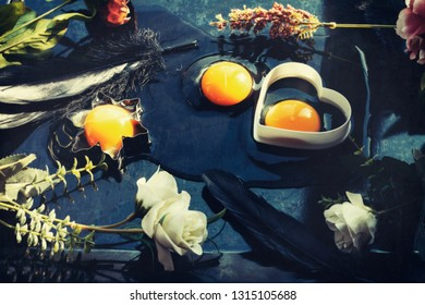 Three raw egg yolks and whites, two in cookie cutters, one spilled on a table, decorated with spring flowers and black feathers for Easter holiday