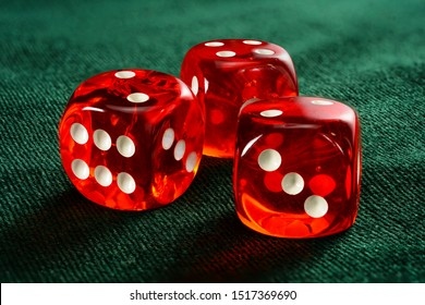 Three red acrylic transparent dices for games. Gambling translucent dices on dark-green velvet surface, close up, large depth of field.