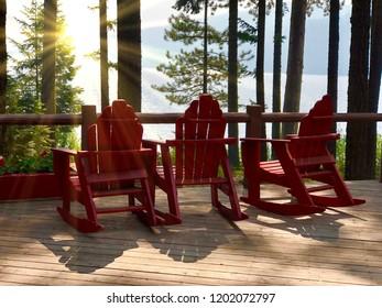 Three red Adirondack chairs overlooking lake