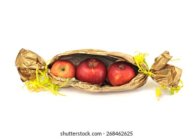Three red apples in foil in the form of candy on a white background