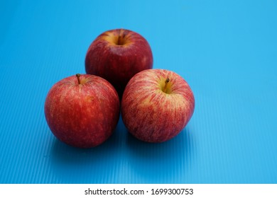 Three red apples on blue background
