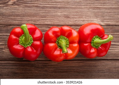 Three red bell peppers on a wooden background. Top view