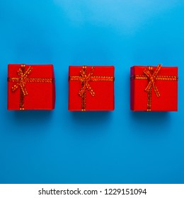 Three red boxes with Christmas gifts lie on a blue background. Web design. For the blog.