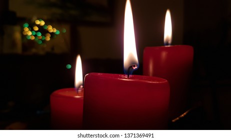 Three red candles sideview. Candlelight flames on burning wickes closeup. Glowing fire of candlesticks in darkness. Christmas candles with blurred colorful Christmas lights on background.