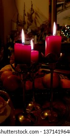 Three red candles in vintage copper candelabras on dinner table. Candlelight flames of cylindrical red wax candles. Burning fire of candlesticks on Christmas holiday table.
