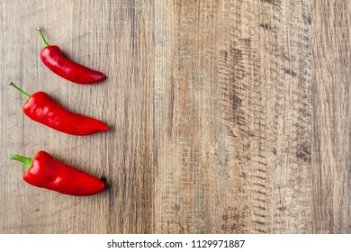 Three red chilli pepper on wooden table
