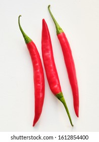 Three red chillies on plain background