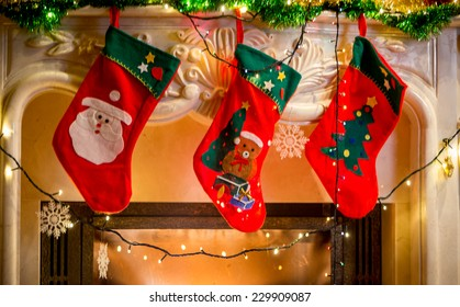 Three red christmas stockings hanging on decorated fireplace