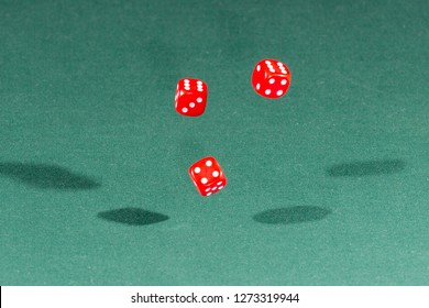 Three red dices falling on a isolated green table