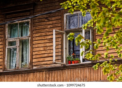 Three red flower pots stand on an open window of an old wooden house. The house is located in Tallinn, Estonia.