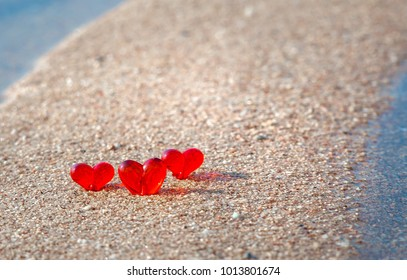 three red glass hearts on white sand, beautiful postcard backgro