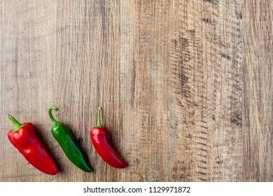 Three red and green chilli pepper on wooden table