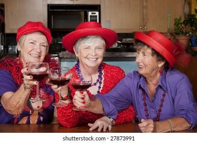 Three red hat ladies toasting with big wine glasses