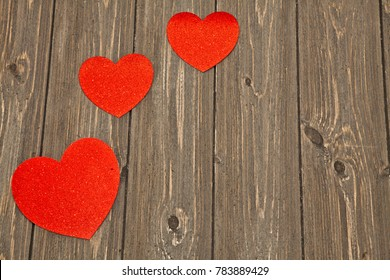 Three red hearts on barn wood planks with copy space.