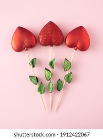 Three red hearts on a twig like flowers. Concept of Valentines day on pink background.